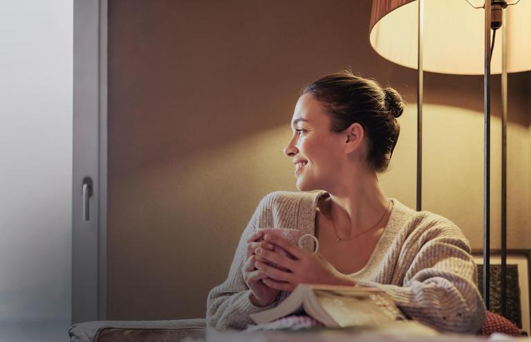 Woman is sitting comfortably with a cup under a warm glowing lamp